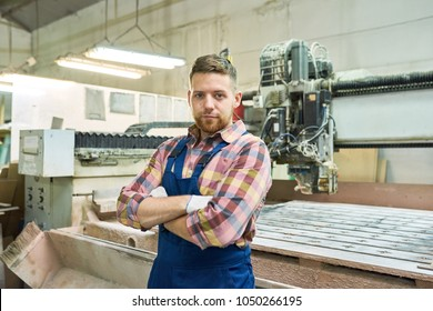 Waist up portrait of young factory worker looking at camera while standing with arms crossed posing by wood cutting machine in modern workshop, copy space