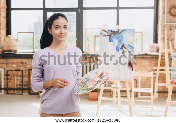 Waist up portrait of young female artist holding palette posing in art studio standing against paintings, copy space