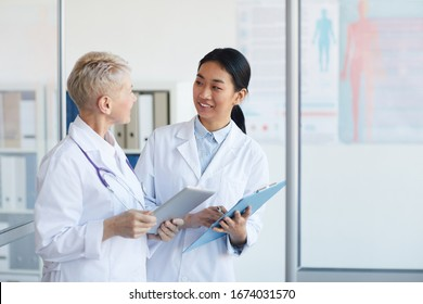 Waist up portrait of young female doctor talking to supervisor and smiling cheerfully while standing in medical office interior, copy space
