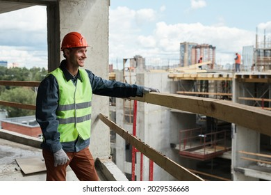 Waist up portrait of young man working at construction site and looking at cityskape, copy space