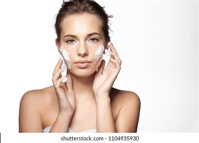 Waist up portrait of young pretty woman applying foaming cleanser. Lovely female with clean fresh perfect skin looking at camera with calmness. Skincare concept. Isolated on white background