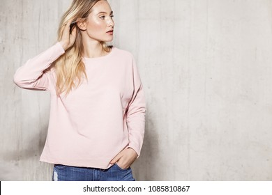 Waist up portrait of young stylish woman in pink sweater. Alluring girl with delicate make-up touching her amazing long hair and looking away thoughtfully. Copy space in right side