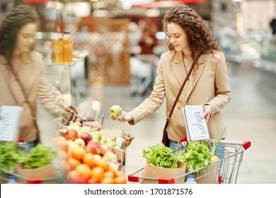 Waist up portrait of young woman choosing fresh organic fruits while buying groceries at farmers market or supermarket, copy space on right