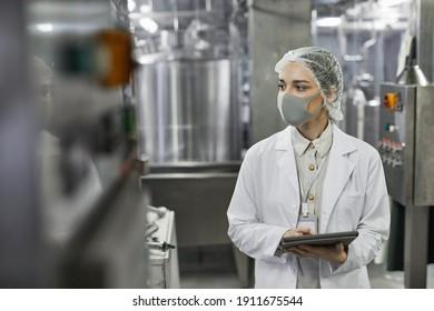 Porträt junger Frauen, die Maske tragen und digitale Tablette bei der Qualitätskontrolle in der Lebensmittelfabrik aufbewahren, Kopienraum