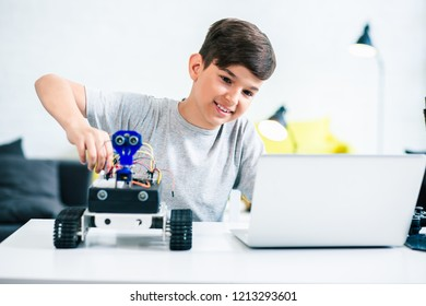 Waist up of a positive little boy sitting at the table and constructing modern robot at home