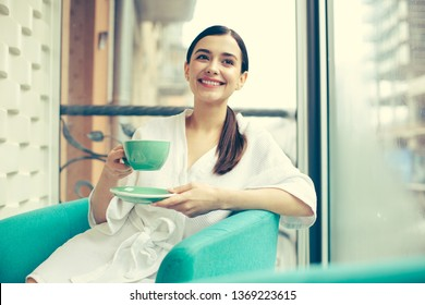 Waist up of a positive relaxed woman wearing a white bathrobe and looking happy while sitting with a cup of tea