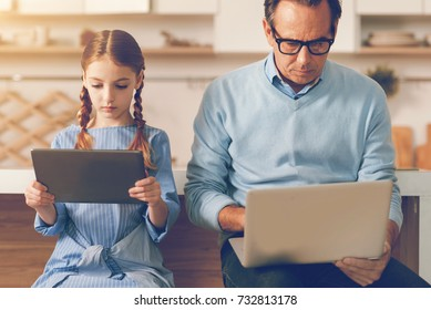 Waist up shot of absorbed father and daughter using computers