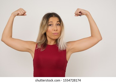 Waist up shot of caucasian woman raises arms to show her muscles feels confident in victory, looks strong and independent, smiles positively at camera, stands against gray background. Sport concept.