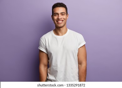 Waist up shot of handsome cheerful man with toothy smile, muscular arms, being in high spirit as spends free time with friends or girlfriend, wears casual white t shirt, isolated over purple wall