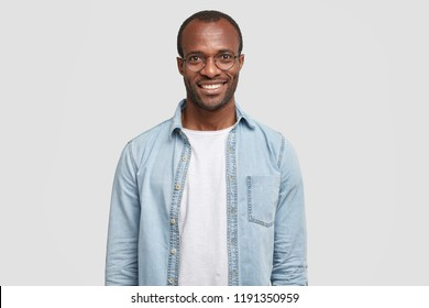 Waist up shot of handsome self confident cheerful male entrepreneur has broad smile, wears round transparent glasses, happy to meet with colleague, dressed in fashionable denim shirt isolated on white