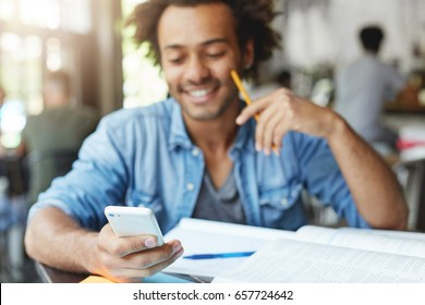 Waist up shot of happy Afro American college student with cute smile typing text message on electronic gadget, sitting at cafe table with textbooks. Selective focus on man's hand holding cell phone