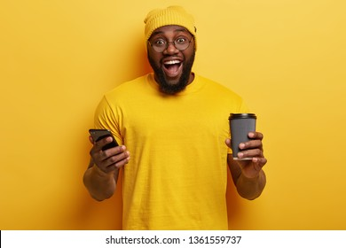 Waist up shot of happy ethnic hipster develops personal website on cell phone, connected to wireless internet, holds disposable cup of hot drink, has thick stubble, wears yellow hat and t shirt