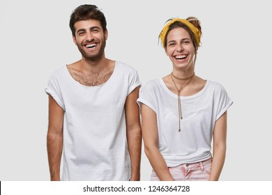Waist up shot of happy female and male fellows dressed in white mockup t shirt, smile broadly, being in high spirit, stand closely to each other, isolated over studio wall. Husband and wife indoor
