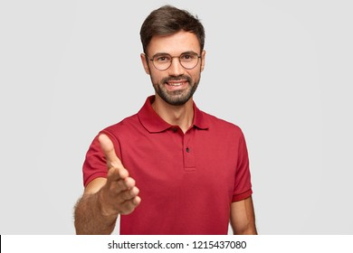 Waist up shot of happy unshaven man gives handshake, greets with someone, smiles sincerely, rejoices meeting, dressed in red t shirt, isolated over white, stretches hand in camera. Nice to meet you