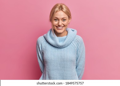Waist up shot of pleased blonde European woman with glad tender expression keeps hands behind back dressed in knitted blue jumper expresses happy emotions isolated over pink studio background.