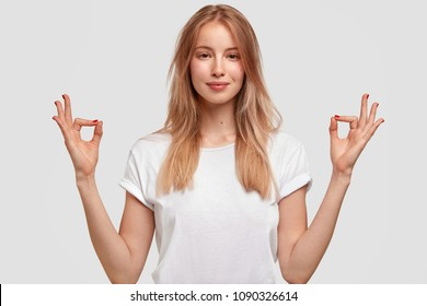 Waist up shot of pretty female with lovely appearance, wears casual t shirt, makes mudra sign, practices yoga as wants to relax, isolated over white background. Caucasian woman in lotus pose