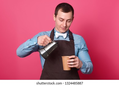 Waist up shot of professional male barista pours coffee from coffeemaker into paper cup, wears shirt and apron, white bowtie poses against pink background, enjoys pleasant aromat of hot beverage