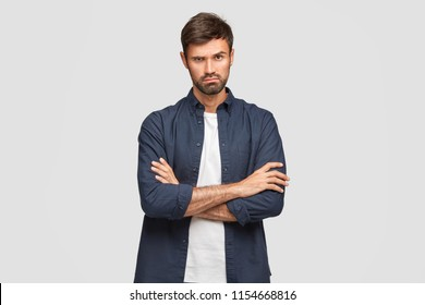 Waist up shot of serious unshaven male with confident expression, keeps arms folded, listens necessary information attentively, wears stylish shirt, poses against white studio wall. People, lifestyle