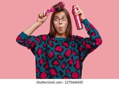 Waist up shot of surprised awkward woman combes fringe, sprays for making haircut, wears big spectacles, sweater, wants to have perfect coiffure, isolated over pink studio wall. Feminity concept