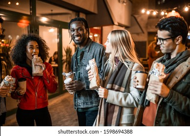 Waist up of smiling friends holding coffee and snacks on the street stock photo