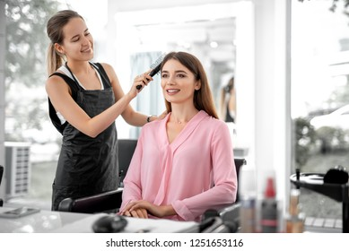 Waist up of smiling lady looking in the mirror while female stylist combing her hair