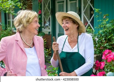 Waist Up of Two Senior Women Having Enjoyable Conversation and Laughing in Home Garden on Summer Day