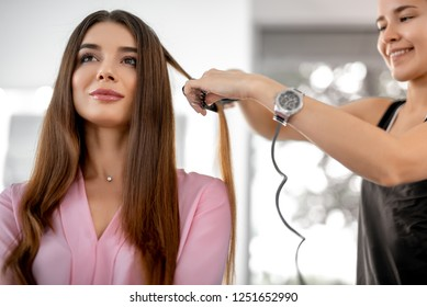 Waist uo photo of cute lady is sitting in beauty zone while female hairdresser doing styling