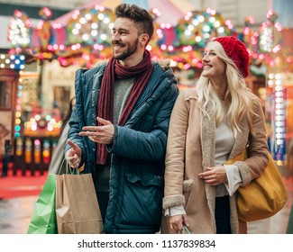 Waist up, front view of a couple walking on a city street with shopping bags in their hand.