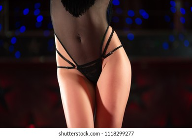 Waist of the young girl. She has attractive black underwear, which highlights her figure. Good bends of the body, women's energy is felt. On the background is colored lights.