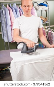 Waist Up of Young Man Wearing White Undershirt Standing in front of Rack of Clothing and Ironing White Shirt Garment with Modern Iron Appliance