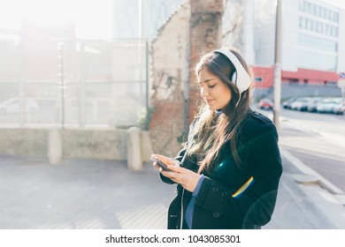 Waist up of young woman posing in the city listening music woth head phones using smart phone hand hold - technology, music, social networking concept