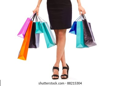 Waist-down view of young woman carrying colorfull shopping bags