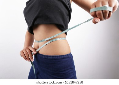 waistline asian woman. Weight loss, slim body healthy lifestyle concept. Fit fitness girl measuring her waistline with measure tape on white background.
