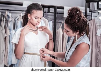 Waistline of model. Busy curly designer with hair bun measuring waistline of her slim beautiful elegant model