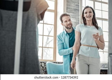 Waistline of wife. Bearded husband working as fashion designer measuring waistline of wife
