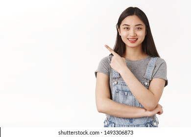 Waist-up friendly enthusiastic cute asian brunette girl explain cool place hang out show useful link pointing upper left corner smile recommend awesome product treat acne prone skin white background
