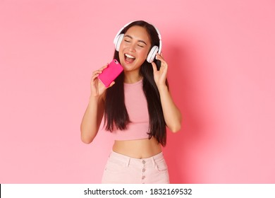 Waist-up portrait of attractive stylish asian girl close eyes and singing along song while listening music in headphones, playing karaoke game on mobile phone, standing over pink background