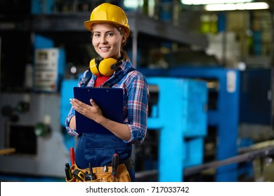 Waist-up portrait of attractive young technician in checked shirt and overall looking at camera with wide smile while carrying out inspection at production department of plant, blurred background