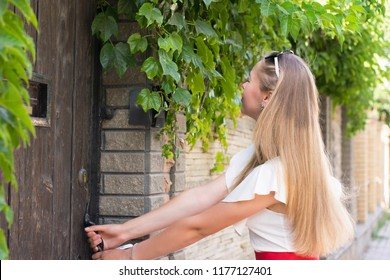 Waist-up portrait of blonde woman trying to open door surrounded with plants. Long-haired model making efforts to get inside. Lifestyle and curiosity concept