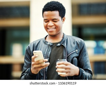 Waist-up portrait of cheerful African man walking down street with coffee cup in his hand, reading messages on his phone and smiling