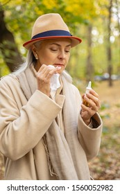Waist-up portrait of a focused sick mature lady looking at her nasal drops
