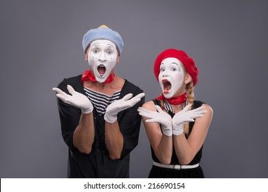 Waist-up portrait of funny mime couple with white faces solemnly singing and waving their hands isolated on grey background with copy place