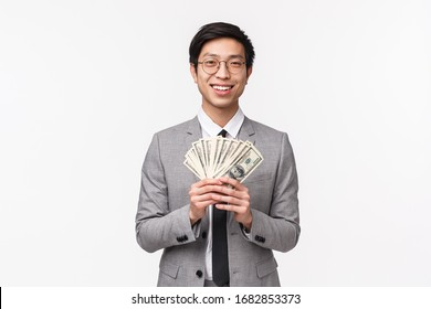 Waist-up portrait of glad handsome asian rich businessman in glasses and suit, showing his money, holding dollars and smiling at camera with satisfied expression, earning big sum, white background