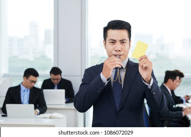 Waist-up portrait of handsome Asian entrepreneur wearing classical suit blowing whistle and showing yellow card to camera, interior of busy open plan office on background