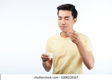 Waist-up portrait of handsome Asian man with closed eyes standing against white background and enjoying taste of yogurt