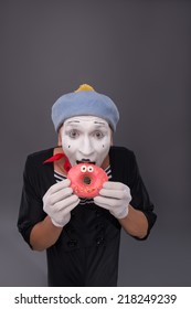 Waist-up portrait of handsome male mime holding with both hands and eating a tasty pink donut with funny eyes while looking at the camera isolated on grey background with copy place