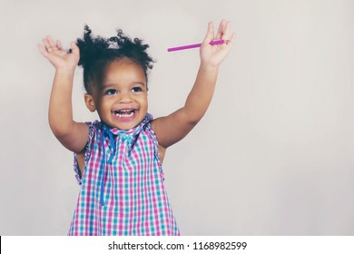 Waist-up portrait of happy african american baby girl holding hands up and laughing. Little child with wide smile and bright dress. Isolated on white background with copy space in right side