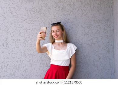 Waist-up portrait of happy girl looking excited about taking selfie on smartphone. Brightly dressed smiling cute blonde preparing to online communication. Isolated on grey