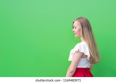 Waist-up portrait of long-haired blonde woman looking and facing something. Model wearing nice white blouse and red skirt. Copy space in left side. Isolated on green background