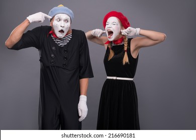 Waist-up portrait of mime couple with white faces, female mime closing her ears with her fingers and shouting on male mime showing that she is crazy isolated on grey background